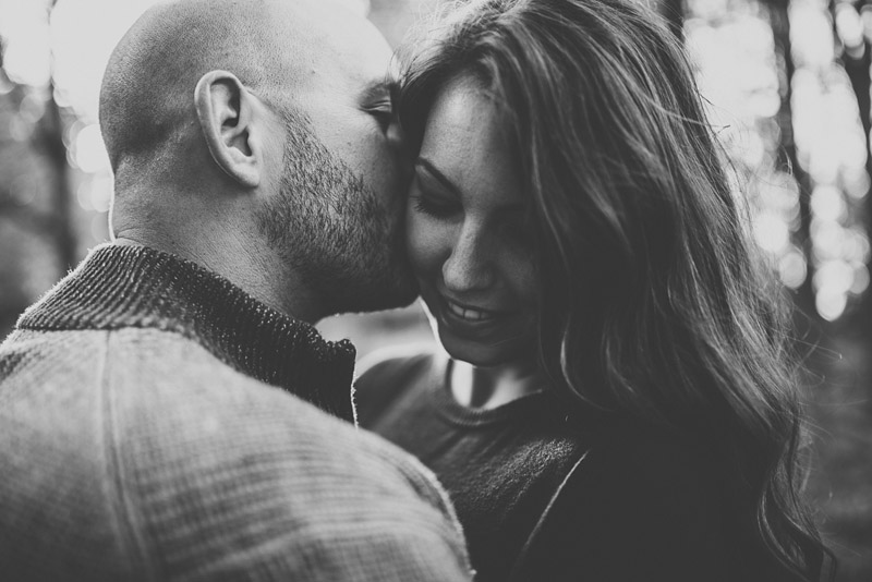 man kissing woman on the cheek during engagement session in Peterborough