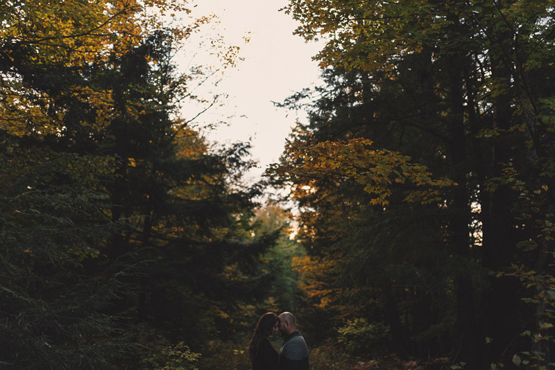 Couple standing in front of beautiful fall forest