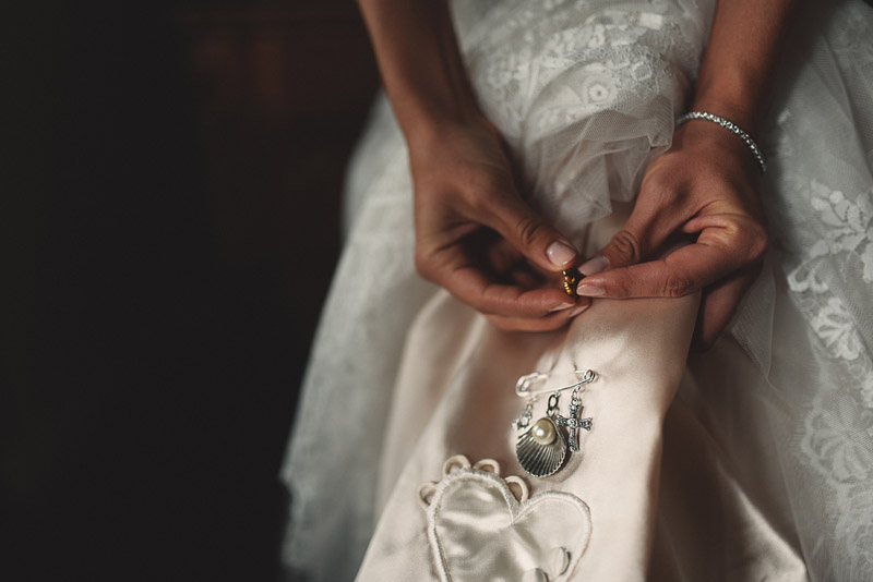 bride buttoning heirloom broach