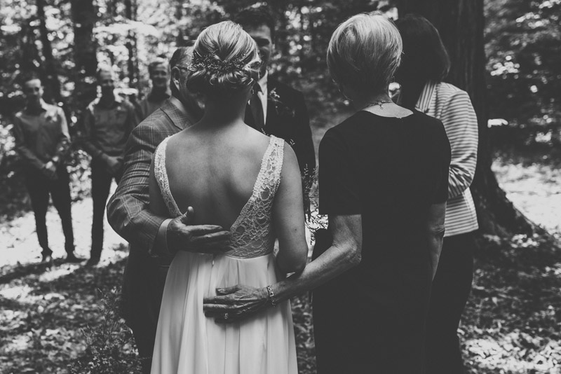 mother and father of bride giving her away during intimate forest ceremony