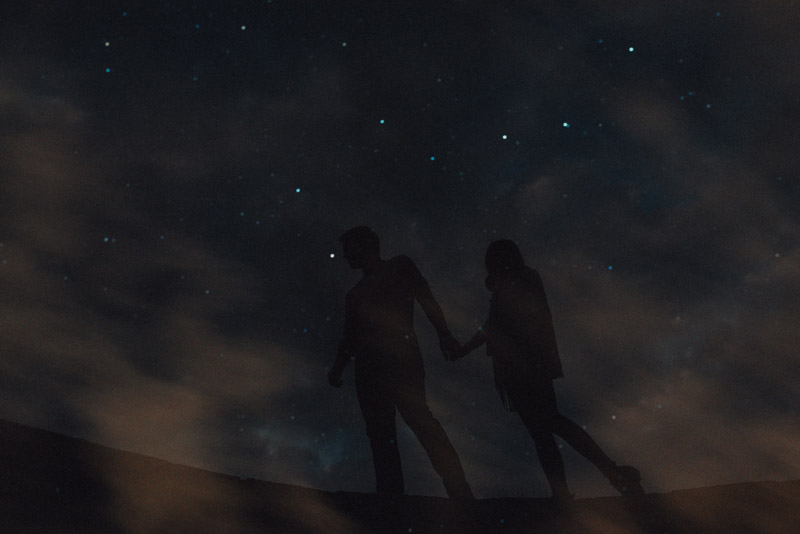 double exposure of the night sky and a couple holding hands