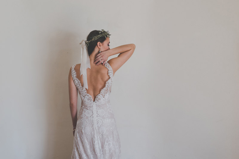 styled bride gently touching the back of her neck