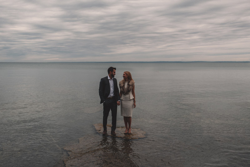 couple standing on rock in the water