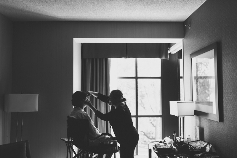 makeup artist doing brides makeup in front of large window in hotel