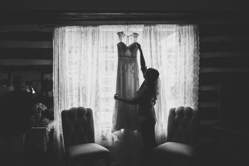 bride hanging dress in window