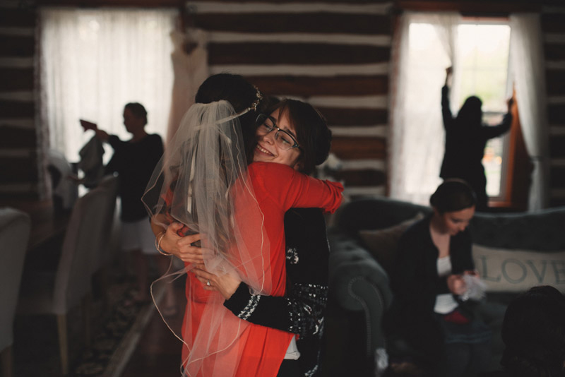 bride hugging bridesmaid as they get ready together