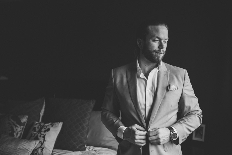 groom looking towards window while doing up suit jacket