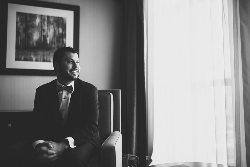 black and white photo of groom looking out window and smiling