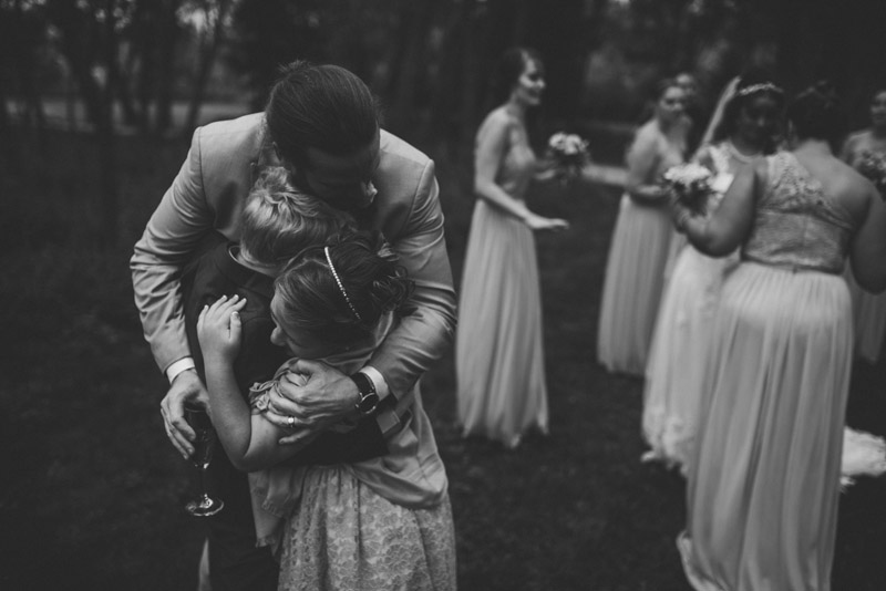 groom hugging children at wedding