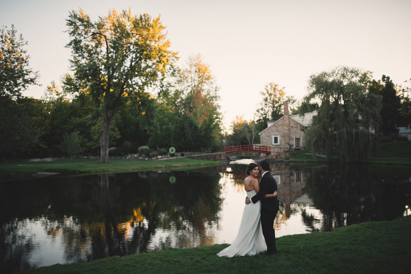 couple in front of pond in wedding attire