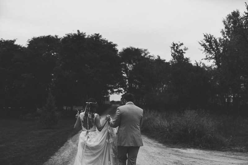 bride and groom holding hands and walking down tree canopy covered driveway