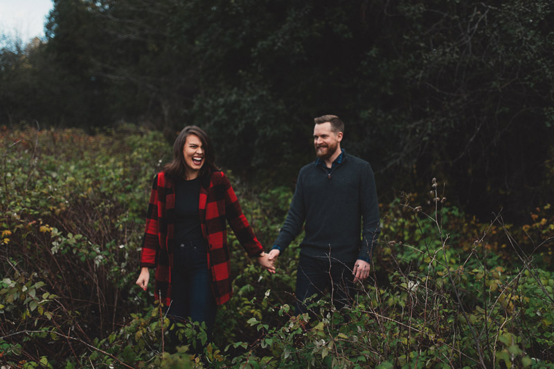 couple holding hands in tall foliage