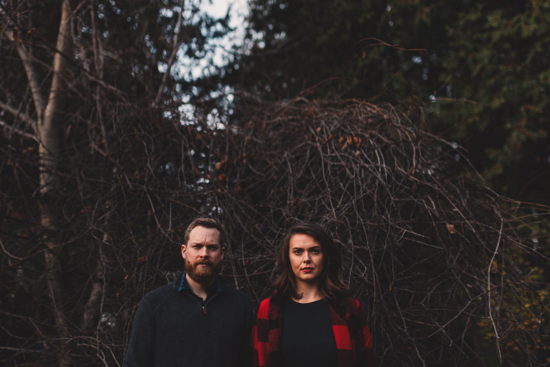 trendy couple looking stoic in front of dead vines