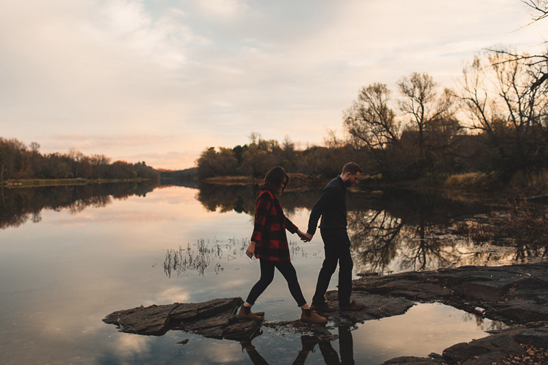 couple walking on rivers edge holding hands