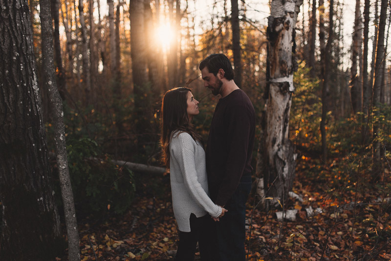 couple looking at each other in forest while sun sets behind them