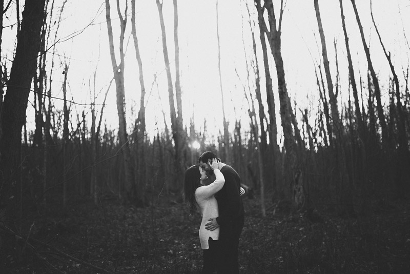 black and white image of couple in dead wood forest