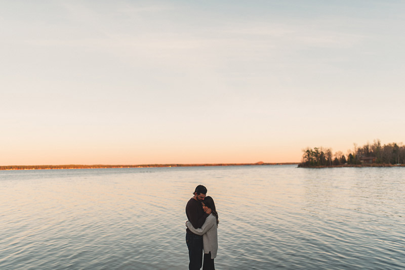 couple embracing in front of large body of water