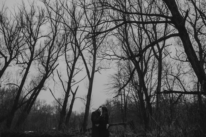 moody black and white image of couple in deadwood forest
