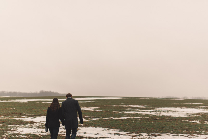 couple walking through farm field together in the snow