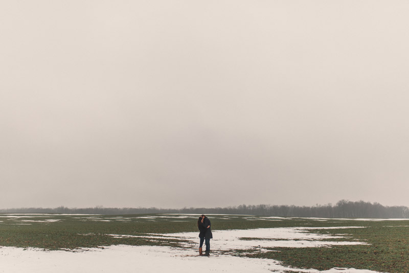 couple standing in vast snow covered field